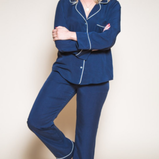 Woman wearing the Carolyn Pajamas sewing pattern by Closet Core Patterns. A Pyjama pattern made in cotton flannel, linen, cottons, lawn or silk fabric featuring a classic notched collar, curved hem, breast pocket and button front top. The straight-legged trousers have an elasticated waist, both have piping detail.