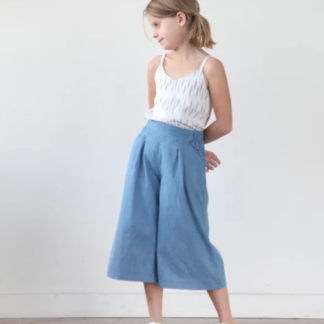 Girl wearing the Children's Mini Emerson Crop Pant sewing pattern by True Bias. A trouser pattern made in cotton, linen, rayon challis or chambray fabric featuring an elasticated back and flat front waistband that sits just below the natural waist, front pleats and side pockets.