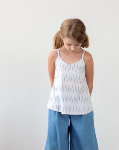 Girl wearing the Children's Mini Ogden Cami sewing pattern by True Bias. A camisole pattern made in cotton voile, cotton lawn, linen or double gauze fabric featuring a soft V neck and spaghetti straps over each shoulder.