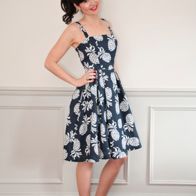 Woman wearing the Rosie Dress sewing pattern from Sew Over It on The Fold Line. A sleeveless dress pattern made in cotton poplin, cotton lawn, linen, seersucker or broderie anglaise fabrics, featuring a boned bodice, low square neckline, full skirt with box pleats at the front and gathers to the side and back, invisible zip centre back closure, narrow shoulder straps and knee length finish.