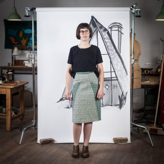 Woman wearing the A-Frame Skirt sewing pattern by Blue Prints for Sewing. A pencil skirt pattern made in denim, twill, sateen, linen, corduroy, rayon challis or linen blend fabrics, featuring a knee length finish, front pockets and kick pleat at the centre back seam.