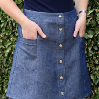 Woman wearing the Ally Skirt sewing pattern by Blue Dot Patterns. A fitted, six gore skirt pattern made in medium weight denim, corduroy, twill, linen or poplin fabrics, featuring a button front, top stitching and pockets.