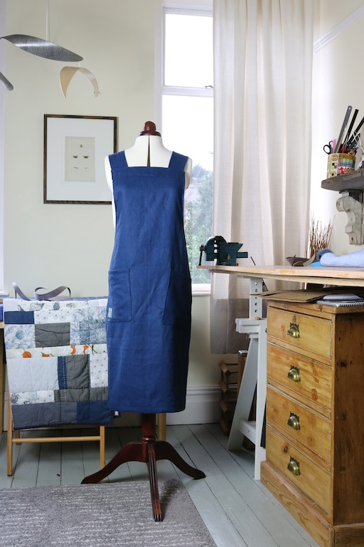 Mannequin wearing the Hepworth Apron sewing pattern by Jenni Smith. An apron pattern made in cotton, linen or denim fabrics featuring front pockets and cross over back straps.