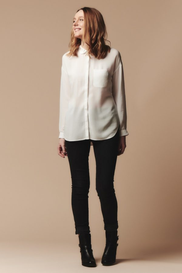 Woman wearing the Melilot Shirt sewing pattern by Deer and Doe. A casual shirt pattern made in batiste, cotton satin, viscose, silk or flannel fabric featuring dropped shoulders, long sleeves with cuffs, and a rounded collar.