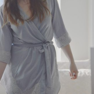 Woman wearing the Inara Robe sewing pattern by Goheen Designs. A cross over robe made in lightweight knit or woven, fabrics, featuring three quarter length sleeves, curved hem that comes up on the sides, bound front edges and belt.