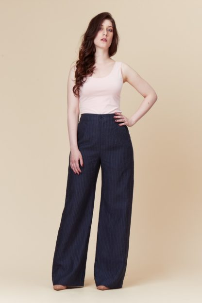 Woman wearing the Narcisse Pants sewing pattern by Deer and Doe. A trouser pattern made in lightweight twill, denim, linen or chambray fabric featuring a high waist, wide legs, inseam front pockets and decorative side stripes.