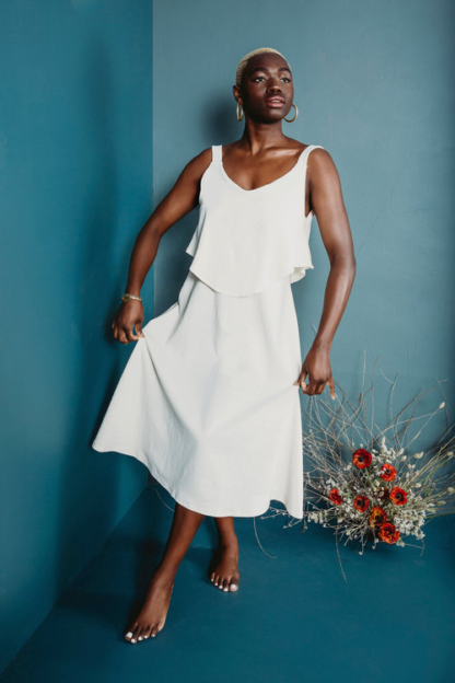 Woman wearing the Hilo Dress sewing pattern by Friday Pattern Company. A sleeveless, loose, flowy, boho style dress pattern made in knits or jersey fabric featuring a low cut neckline and an extra top bodice layer.