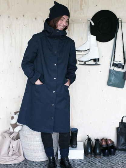 Woman wearing the Hoodie Parka Coat sewing pattern by The Assembly Line. An A-line shaped coat pattern made in canvas, cotton twill or denim featuring snap button closing, large front pockets and hood.