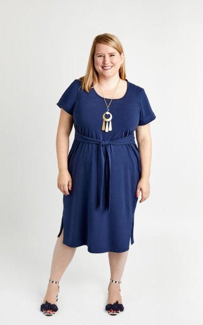 Woman wearing the Pembroke Dress sewing pattern by Cashmerette. A T-shirt dress pattern made in mid-weight knit fabric such as cotton/lycra, poly/lycra or rayon jersey fabric featuring a scoop neckline, side slits, short sleeves and a waist front tie.