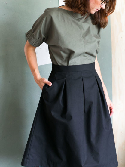 Women wearing the Three Pleat Skirt sewing pattern by The Assembly Line. A pleated skirt pattern made in denim, cotton twill or canvas fabric featuring a right side pocket, and left side zipper opening.