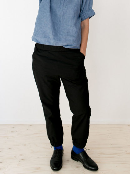 Woman wearing the Almost Long Trousers sewing pattern by The Assembly Line. A relaxed fitting trouser pattern made in cotton twill, denim or canvas fabric featuring a tapered leg with elasticated bottom cuffs and inseam pockets.