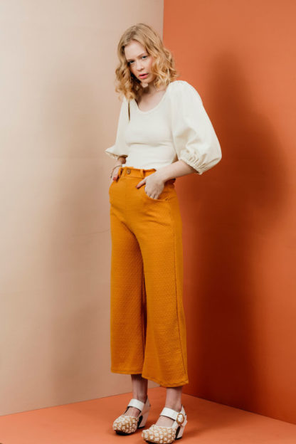 Woman wearing the Joan Trousers sewing pattern by Friday Pattern Company. A trouser pattern made in knit fabrics featuring wide legs, waistband, scoop pockets and single button closure.
