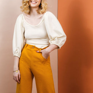 Woman wearing the Adrienne Blouse sewing pattern by Friday Pattern Company. A blouse pattern made in knits or jersey fabric featuring billowy statement sleeves that are gathered up at the shoulders and a medium low round neckline.