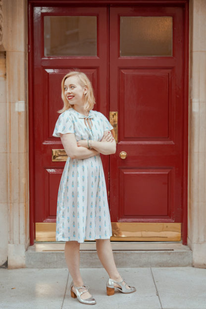 Women wearing the London Dress sewing pattern from Selkie Patterns on The Fold Line. A dress pattern made in light or medium weight cotton or bamboo fabrics, featuring short raglan sleeves, knee length skirt, keyhole neckline with neck tie and loose bodice pleats.