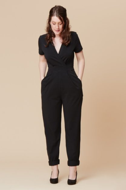 Woman wearing the Sirocco Jumpsuit sewing pattern by Deer and Doe. A dungaree pattern made in medium weight jersey or interlock knit fabric featuring a mock-wrap, short set-in sleeves and pleated trousers with tapered legs.