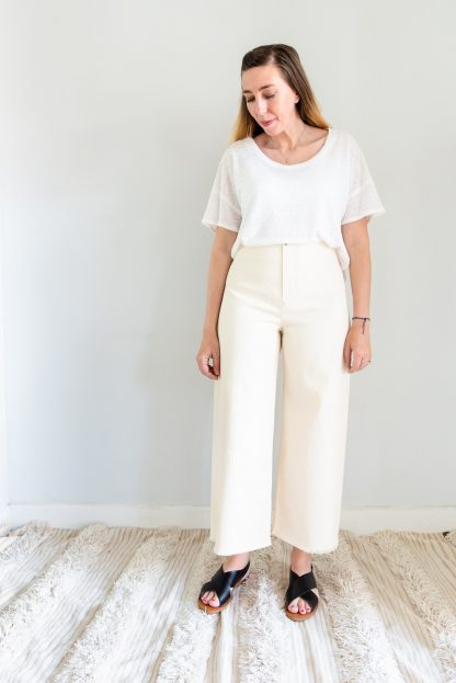 Woman wearing the Parasol Trousers sewing pattern by Ensemble. A trouser pattern made in light to medium weight woven fabrics, featuring a high waist, slanted front pockets, no side seams and front zipper closure.