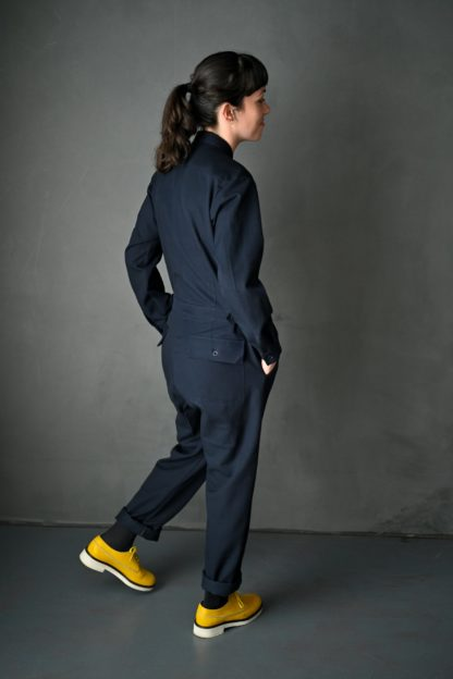 Woman wearing the Thelma Boilersuit sewing pattern by Merchant and Mills. A boilersuit pattern made in twill, denim, cotton poplin or linen fabric featuring a loose fit, back pockets, breast pockets, collard neck, front zip and long sleeves.