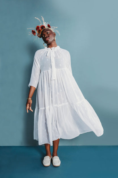 Women wearing the Wilder Gown sewing pattern by The Assembly Line. A loose, flowy, tiered dress pattern made in rayon, silk or linen fabric featuring raglan sleeves and ties at the neck.