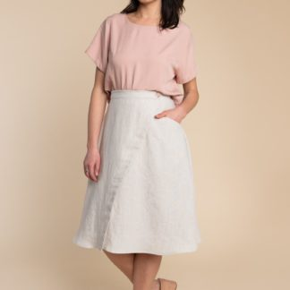 Woman wearing the Fiore Skirt sewing pattern by Closet Core Patterns. An asymmetrical wrap skirt pattern made in linen, chambray, denim or poplin fabric featuring a high waist, and single hip pocket.
