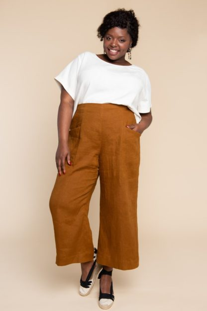 Woman wearing the Pietra Pants sewing pattern by Closet Core Patterns. A trouser pattern made in linen, chambray, lightweight denim or twill fabric featuring a flat front, high waist with elastic at the back and slanted hip pockets.