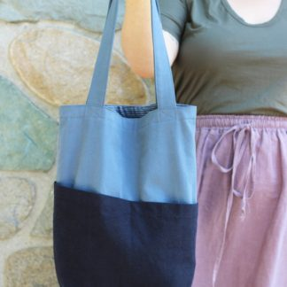 Woman holding the Costa Tote sewing pattern by Helens closet. A shopping bag pattern made in denim, twill or cotton with long handles and four pockets.