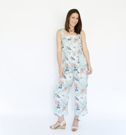 Woman wearing the Frisco Jumpsuit sewing pattern from Threadbear on The Fold Line. A sleeveless jumpsuit pattern made in linen's, chambray, tencel, rayon's or lightweight denim fabrics, featuring a cropped wide leg trouser, the waist is cinched by an elasticised belt that is fastened with a set of D-rings and slash pockets.