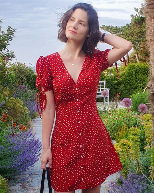 Woman wearing the Etoile Dress sewing pattern by French Poetry. A dress pattern made in silk crepe, viscose, polyester crepe or linen fabrics, featuring a deep V-neck, button front closure, front and back darts and gathered short sleeves with self-fabric ties.