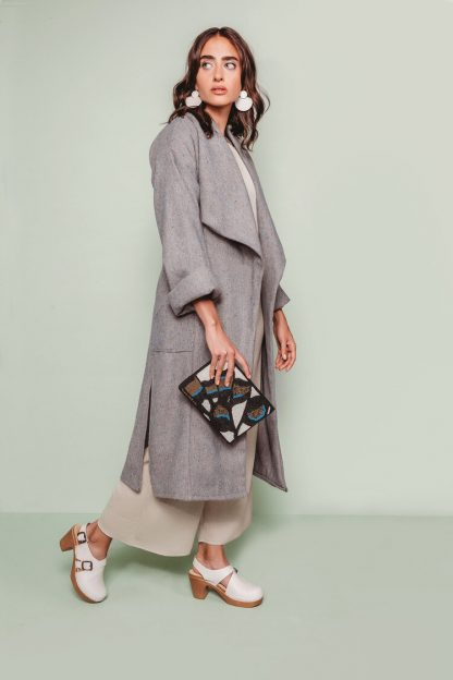 Woman wearing the Cambria Duster Coat sewing pattern by The Assembly Line. A shin length coat pattern made in rayon twill, gabardine, or light wool fabric featuring a dramatic, wide draped shawl-style collar, and side pockets.