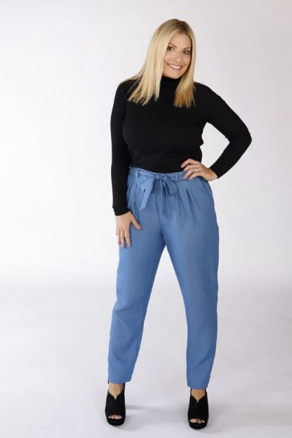 Woman wearing the Crew Trousers sewing pattern by Chalk and Notch. A pleated trouser pattern made in rayon crepe, linens or wool crepe fabrics, featuring a high waist, tapered leg, waist tie and belt loops.