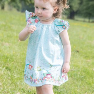 Child wearing the Baby/Child Lillia Rae Dress sewing pattern by Bobbins and Buttons. A dress pattern made in cotton and cotton blends, broadcloth or cotton lawn fabrics, featuring a loose fit, flutter sleeves and elastic neckline.