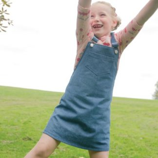Woman wearing the Baby/Child Mary Dress sewing pattern by Bobbins and Buttons. A pinafore dress pattern made in denim, corduroy, needlecord, cotton or cotton blend fabrics, featuring an A-line silhouette, pockets and shoulder straps.