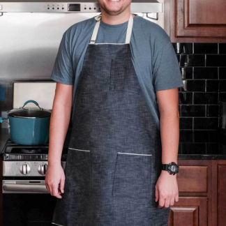 Man wearing the Selvedge Denim Apron sewing pattern by Fancy tiger Crafts. An apron pattern made in denim fabrics, featuring two large pockets, one small breast pocket and twill tape neck and waist ties.