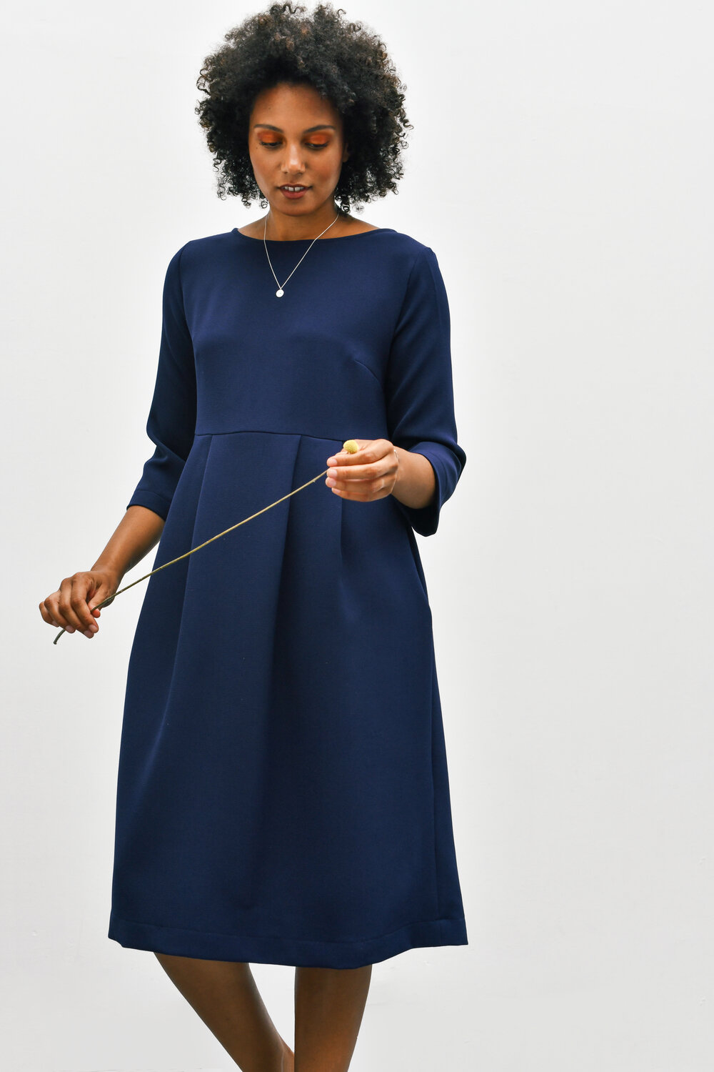Woman wearing the Cissy Dress sewing pattern by Homer and Howells. A dress pattern made in cottons, cords, wool or crepe fabrics, featuring a slightly boxy fit, boat neck, bracelet length sleeves, centre back zip. Deep pleats in the skirt create volume and movement, plus side seam pockets.