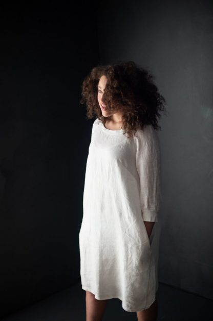 Woman wearing the Fielder Dress and Top sewing pattern by Merchant and Mills. A dress pattern made in linen, cottons, lightweight denims, wools or crepe fabric featuring a round neck, bust darts, three quarter raglan sleeves and in-seam pockets.