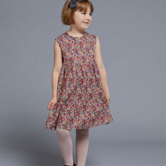 Child wearing the Baby/Child Mabel Tiered Dress sewing pattern by Liberty Sewing Patterns. A sleeveless dress pattern made in cotton or linen fabrics, featuring a gathered tiered dress, back zipper closure and jewel neckline.