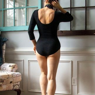 Woman wearing the Nathalie Bodysuit sewing pattern from Untitled Thoughts on The Fold Line. A bodysuit pattern made in knit fabrics, featuring a figure hugging silhouette, low scoop back, low rise leg and full bottom coverage, ¾ length sleeves and armhole darts.
