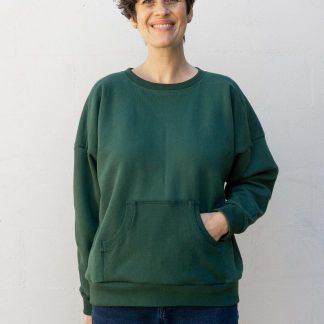 Woman wearing the Ali Sweatshirt sewing pattern from Sew DIY on The Fold Line. A sweatshirt pattern made in medium-weight knit fabrics, featuring drop shoulders, dolman sleeves, shoulder yoke, crew neck and kangaroo pocket.