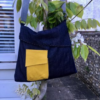 The Almost Square Bag sewing pattern by Dhurata Davies Patterns. A messenger style bag pattern made in medium weight woven fabric, featuring a front patch pocket, angled flap and large zipped pocket on the back.