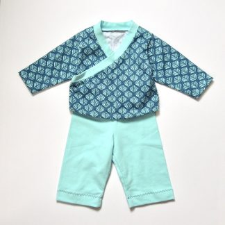 The Babies' Roo Top and Marley Bottoms sewing pattern by Dhurata Davies Patterns. A top and leggings pattern made in lightweight cotton jersey fabric, featuring leggings with an elasticated waist and long sleeved top with a front crossover detail.