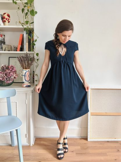 Woman wearing the Paulette Dress sewing pattern by Camimade. A dress pattern made in crepe, viscose, rayon, cotton lawn or cotton sateen fabrics, featuring a Peter Pan collar, front keyhole, cap sleeves and a gathered skirt that is pregnancy friendly due to its empire line. It closes with a side invisible zipper.