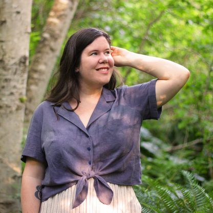 Woman wearing the Gilbert Top sewing pattern by Helens Closet. A button up shirt pattern made in linen, lawn, seersucker and poplin fabric featuring a relaxed fit, breast pocket, short sleeves and tie front.