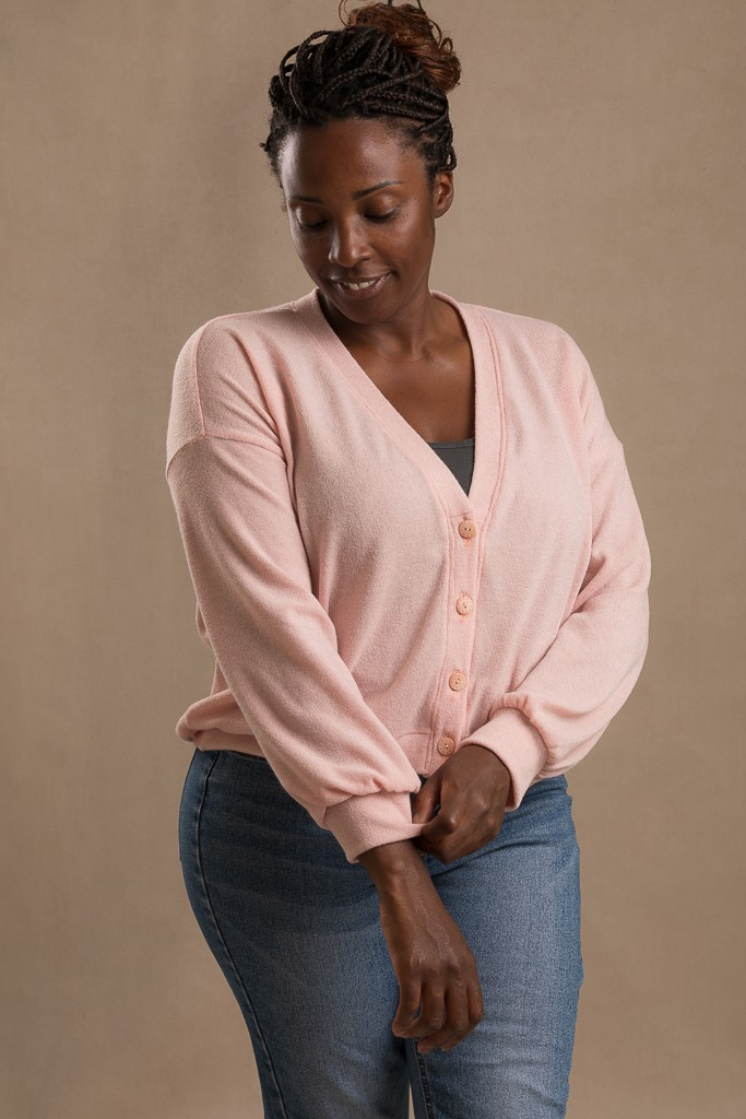 A picture of the Jaimie Cardigan worn in a soft pink jersey fabric by a model.