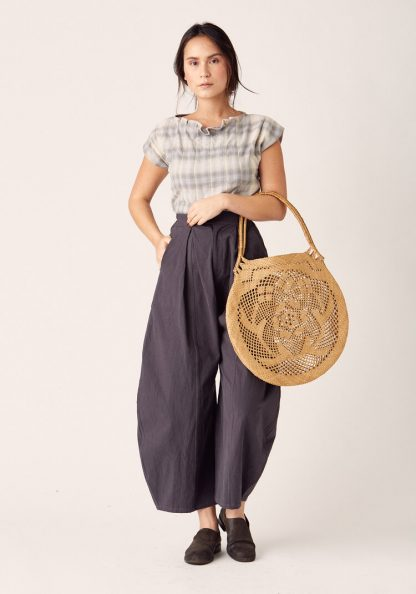 Woman wearing the Arthur Pants sewing pattern by Sew Liberated. A trouser pattern made in linen, gabardine, silk noil, twill, cotton chambray, French terry, interlock or jersey fabrics, featuring wide-legs with dramatically shaped side seams and a tapered hem, high waist, lowered crotch, roomy pockets and zipper fly.