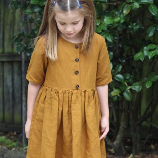 Child wearing the Baby/Child Kauri Dress sewing pattern by Below the Kowhai. A dress pattern made in light to medium weight linen, cotton, flannel or sateen fabrics, featuring a gathered waist, relaxed fit, pockets, elbow length sleeves and button bodice.