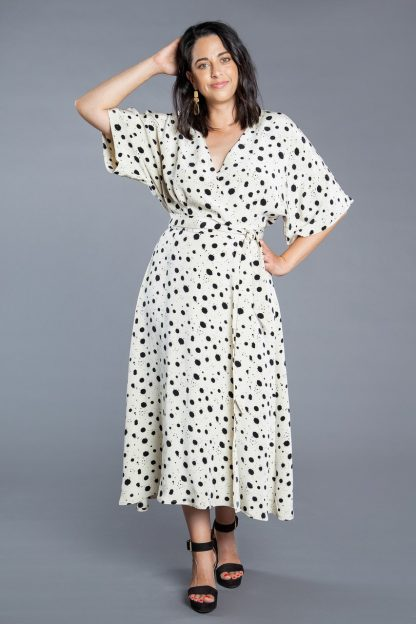 Woman wearing the Elodie Wrap Dress sewing pattern by Closet Core Patterns. A wrap dress pattern made in cotton poplin, linen, batiste or chambray fabric featuring a softly flowing bodice, dolman style sleeves, V-neck and waist tie.