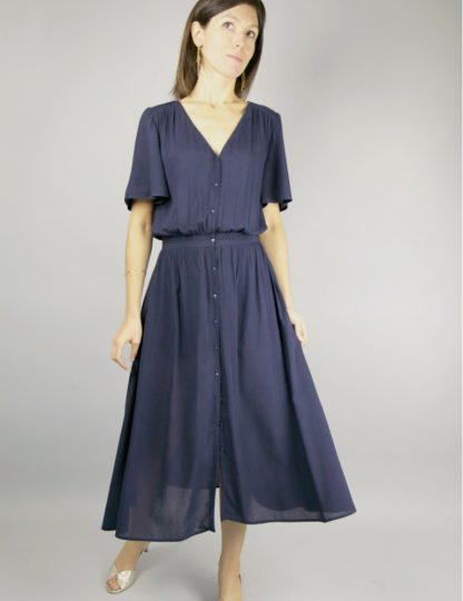 Woman wearing the Harmonie Dress sewing pattern by Atelier Scammit. A waisted, dress pattern made in very light to medium weight batiste, crepe, light denim or viscose fabrics, featuring a V-neck, short sleeves, in-seam pockets and button front closure.