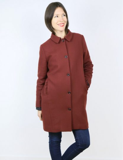 Woman wearing the Merci Coat sewing pattern by Atelier Scammit. A coat pattern made in medium to thick woollens, jacquard or gabardine fabrics, featuring front button closure, collar, pockets and above knee length.