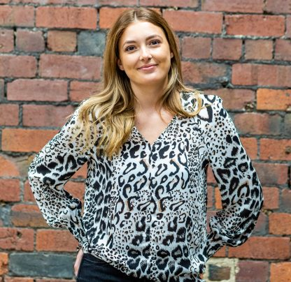 Woman wearing the Florence Blouse sewing pattern from SIZE:me on The Fold Line. A blouse pattern made in viscose, crepe or cotton lawn fabrics, featuring a loose fit, full length sleeves with deep shirred cuffs and a V-neck.