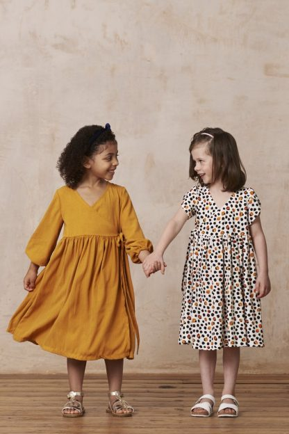 Children wearing the Child/Teen Little Hannah Dress sewing pattern from By Hand London. A dress pattern made in cottons, linens, silks or viscose, featuring a scoop wrap neckline, gathered skirt, short or long sleeves and no zipper.