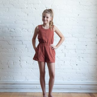 Girl wearing the Children's Mini Nova Jumpsuit sewing pattern by True Bias. A sleeveless jumpsuit pattern made in light to medium knit fabrics fabric featuring a wide elastic waistband, inseam pockets and a round neck.
